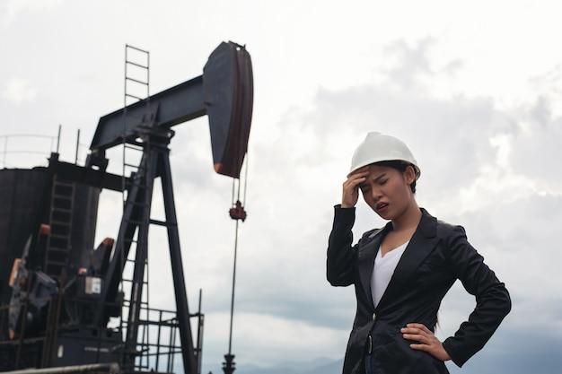 Женский инженер стоя с работая масляными насосами с белым небом.