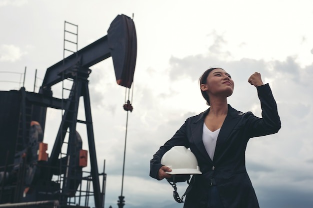 Female engineer standing with working oil pumps with a white sky .