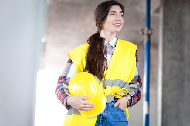 Female engineer stands at a construction site and holding a hardhat in hand