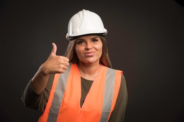 白いヘルメットとギアを身に着けて、親指を立てるサインをあきらめる女性エンジニア。