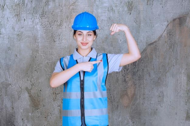 파란색 헬멧과 장비를 착용하고 그녀의 팔 근육을 보여주는 여성 엔지니어.