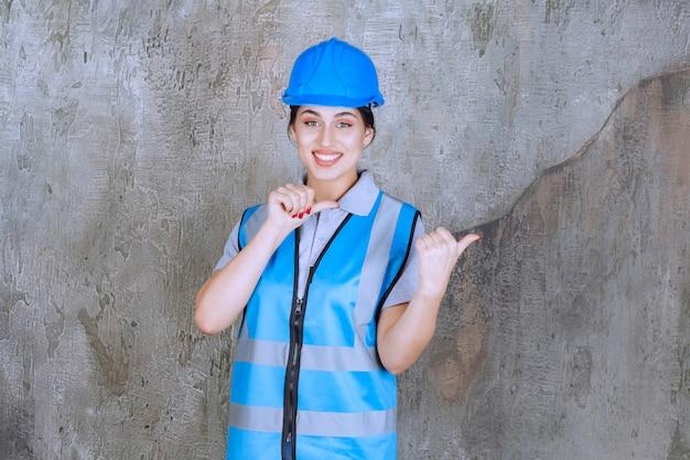 파란색 헬멧 및 장비를 착용 하 고 뒤에 뭔가 보여주는 여성 엔지니어.
