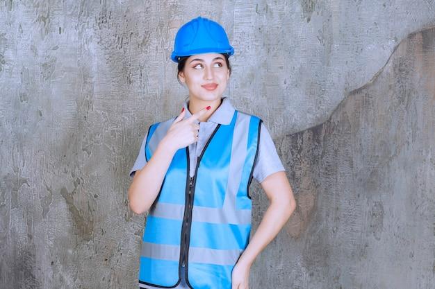 青いヘルメットとギアを身に着けて、右側に何かを示している女性エンジニア。