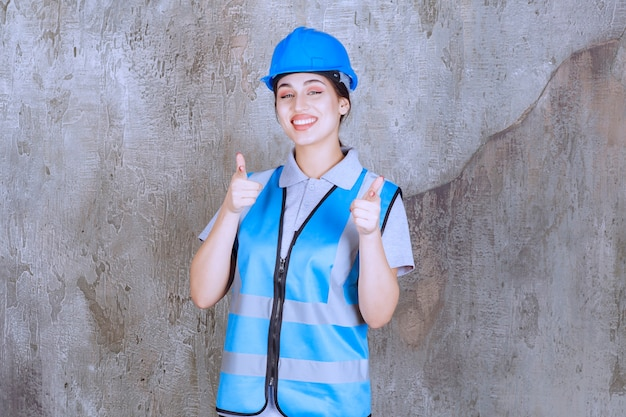 Ingegnere donna che indossa casco blu e attrezzatura e nota la persona davanti.