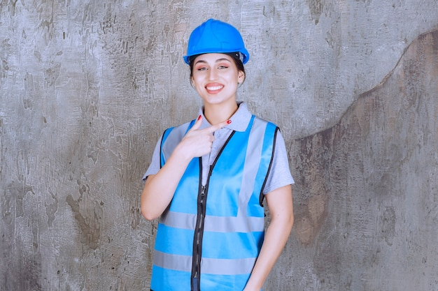 Female engineer wearing blue helmet and gear and showing something on the right.