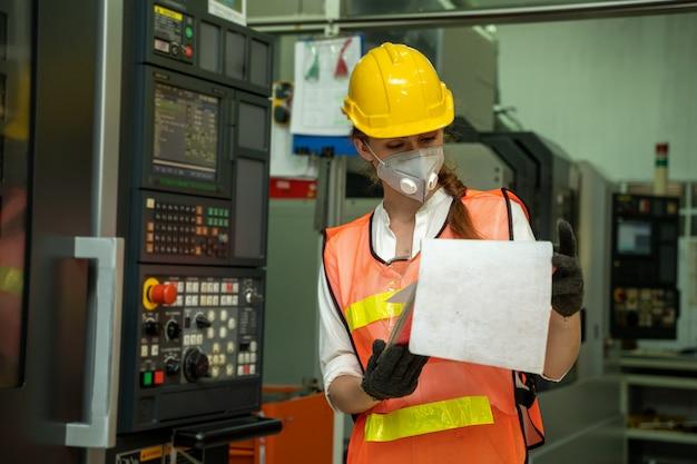 工場でcovid-19から保護するための防護マスクを身に着けている女性エンジニア