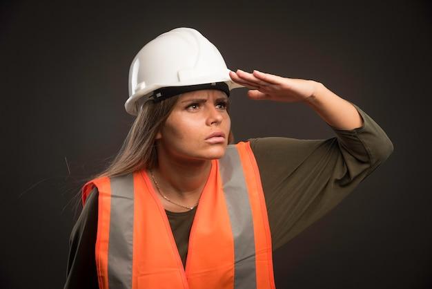 Ingegnere femminile che indossa un casco bianco e attrezzi e guarda avanti.