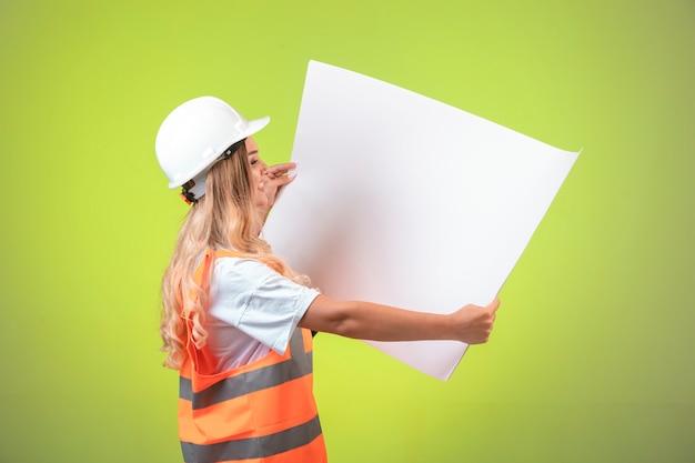 Ingegnere femminile in casco bianco e attrezzi che tengono il piano di costruzione.