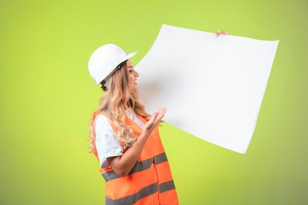 Ingegnere femminile in casco bianco e piano di progetto di lettura degli attrezzi.