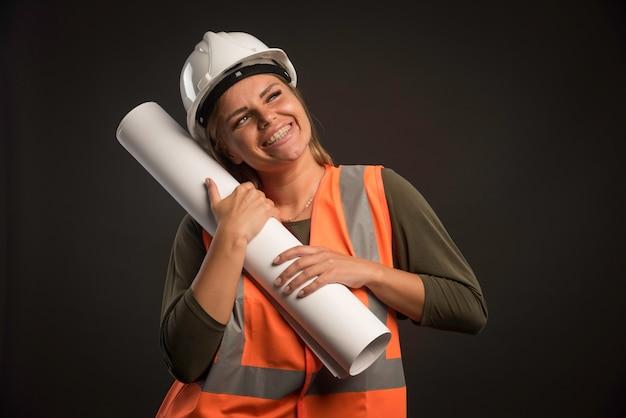 Женский инженер с белым шлемом держит план проекта и выглядит счастливым.