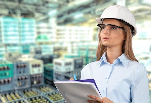 안경을 쓰고 창고에 클립보드를 들고 있는 여성 엔지니어