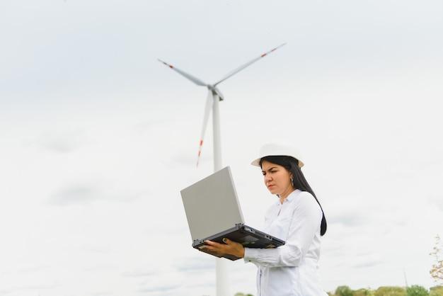 Инженер-женщина в каске на ветряной электростанции, работающей на ноутбуке