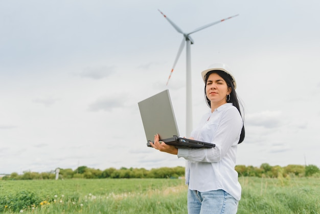 Инженер-женщина в каске на ветряной электростанции, работающей на ноутбуке Premium Фотографии
