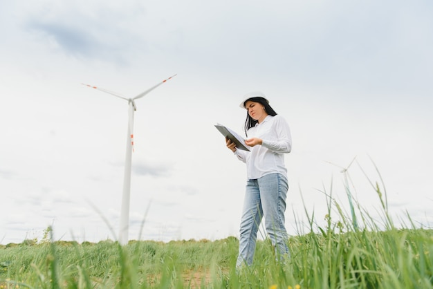 Женщина-инженер в каске на ветряной электростанции Premium Фотографии