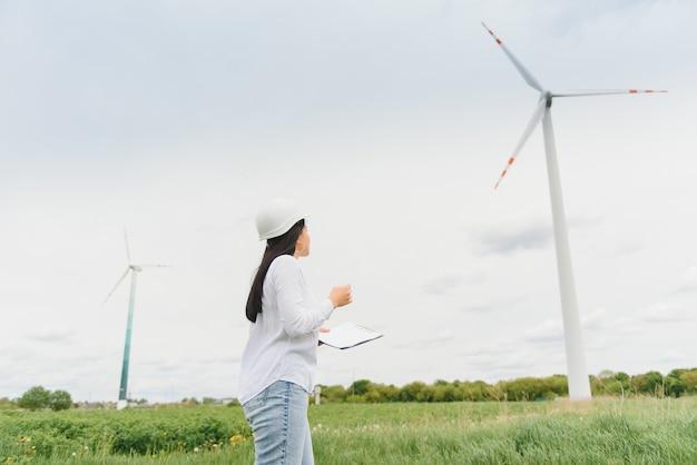 Женщина-инженер в каске на ветряной электростанции