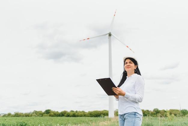 Женщина-инженер в каске работает на ветряной электростанции Premium Фотографии