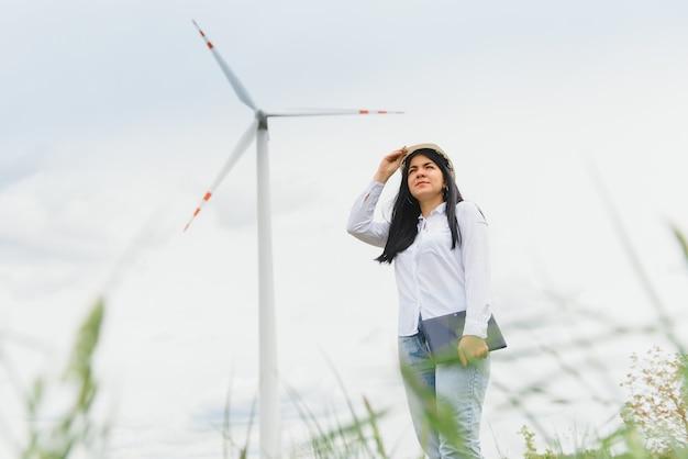 Женщина-инженер в каске работает на ветряной электростанции