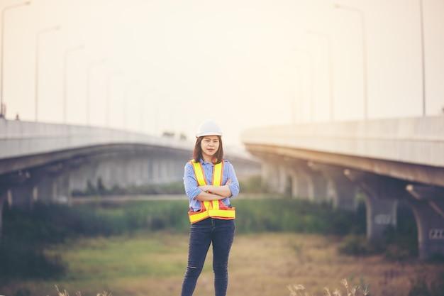 建設現場でokサインとして親指を上げてヘルメットをかぶった女性エンジニア。女性の力、男女共同参画、働く女性、自信のある女性エンジニア