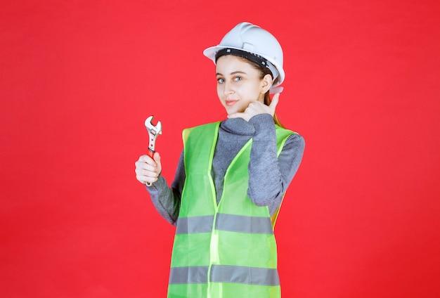 金属製のレンチを持って電話をかける白いヘルメットをかぶった女性エンジニア。
