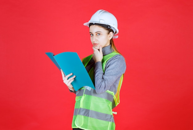 Female engineer with white helmet holding a blue project file,reading it and thinking.