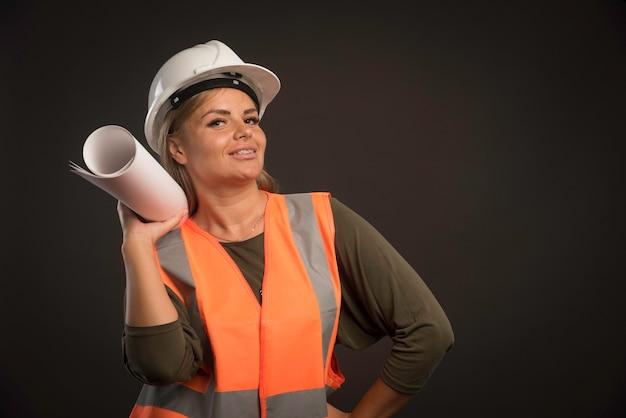 Ingegnere femminile con un casco bianco che tiene il piano di progetto e sembra positivo.