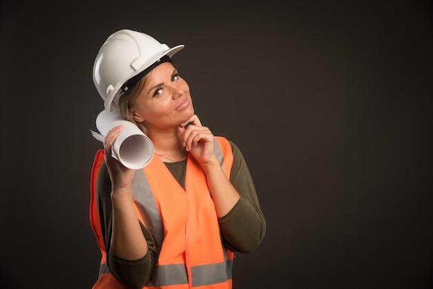 Ingegnere femminile con un casco bianco che tiene il piano di progetto.
