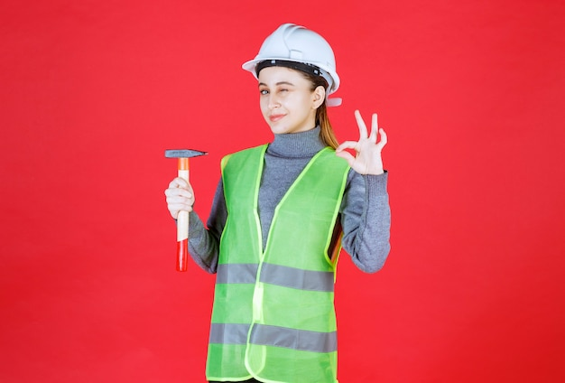 Female engineer with white helmet holding a wooden ax and showing enjoyment hand sign.