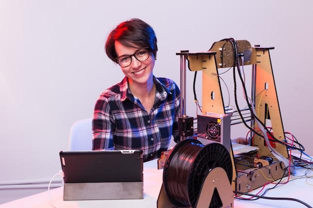 ラボで夜間に働く女性エンジニア、プリンターのコンポーネントを調整している