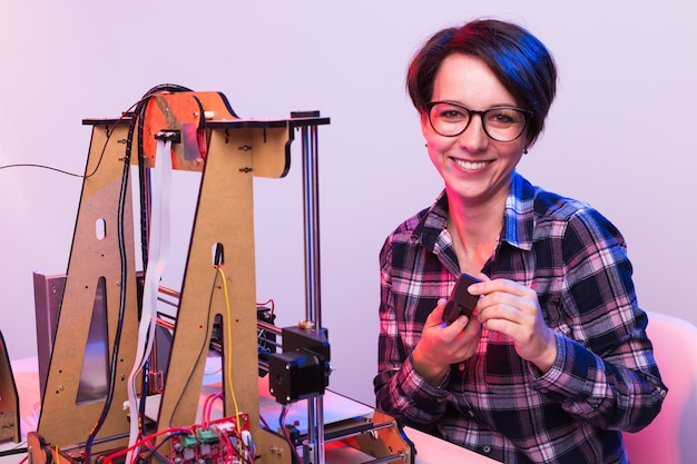 실험실에서 밤에 일하는 여성 엔지니어, 그는 프린터 구성 요소를 조정하고 있습니다.