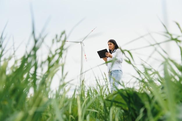 Женщина-инженер, работающая на ветряной электростанции с планшетом