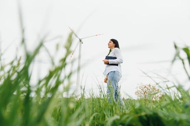 Женщина-инженер, работающая на ветряной электростанции с планшетом Premium Фотографии