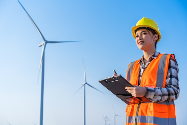 Female engineer working and writing on a clipboard against wind turbine farm