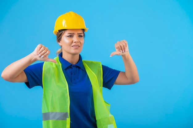 Female engineer in yellow helmet and gear doing thumbs down.