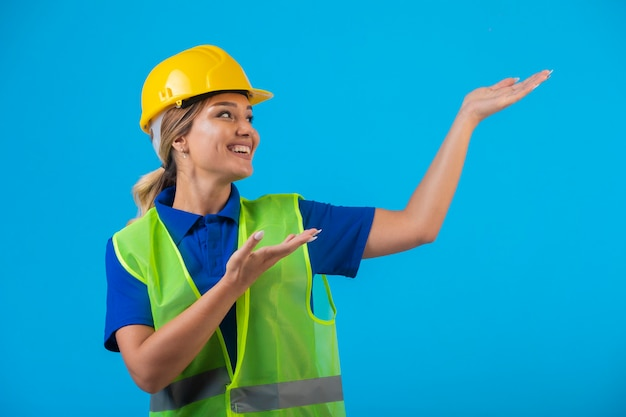 Female engineer in yellow helmet and gear pointing above.