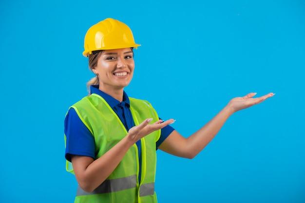 Female engineer in yellow helmet and gear presenting something.