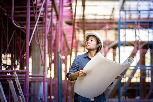 女性工学は足場をチェックします。職長が建設現場を視察します。図面レイアウトを探している青写真を保持しているエンジニアリングの女性。
