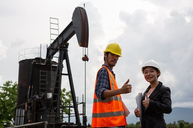 Female engineers consult with workers next to working oil pumps with a sky .