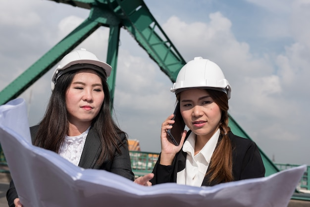 Female engineers hold radio, blueprints and reports, control schedules for employees in the power industry.