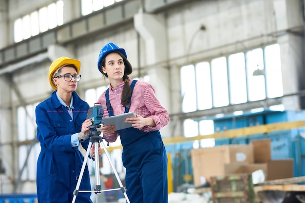 Female engineers using optical level