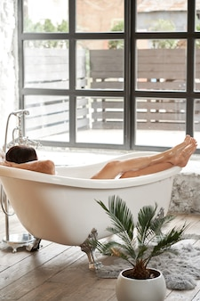 A female enjoy lies in a white bathtub and looks out the street through a large window, back view shot
