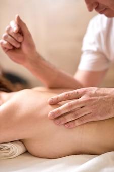 スパで背中と背骨のマッサージを楽しんでいる女性。男性マッサージ師の手に焦点を当てます。閉じる。女性患者を治療するプロのマッサージセラピスト。リラクゼーション、美容、ボディ&フェイストリートメントのコンセプト