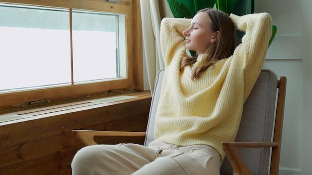 Женщина, наслаждающаяся моментами спокойствия и комфорта, расслабляясь в кресле дома