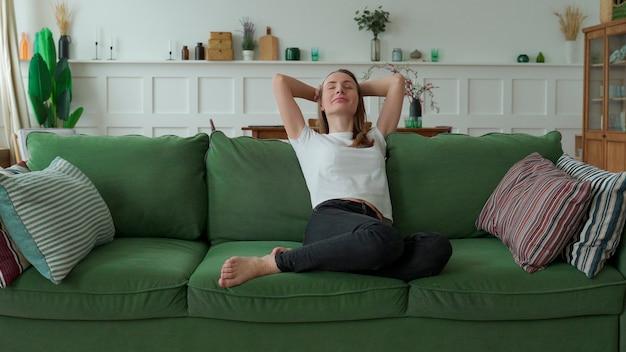집에서 소파에서 편안하게 평온함과 편안함의 순간을 즐기는 여성