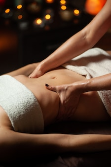 Female enjoying relaxing back massage in cosmetology spa centre.