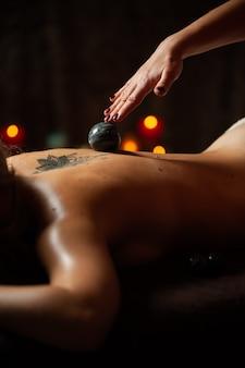 Женщина, наслаждаясь расслабляющим массажем спины в спа-центре косметологии.