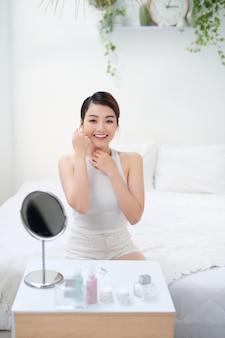 毎日の美容ルーチンと美容トリートメントの後、健康的な輝く肌で楽しむ女性。