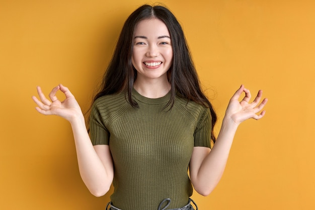 Female enjoys meditation, isolated in studio on yellow background. young woman with long black hair stands smiling in yoga pose, keep calm. yoga concept