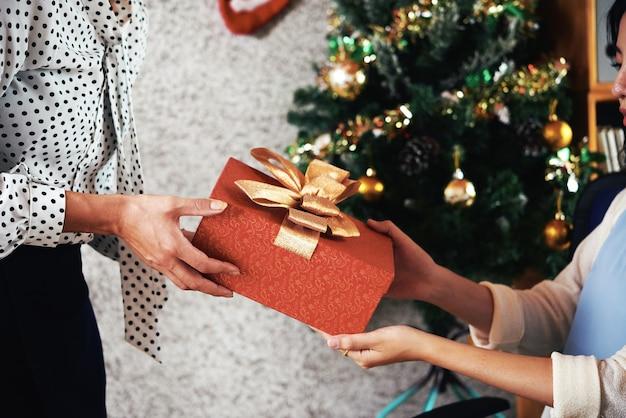 クリスマスプレゼントを与える女性起業家は彼女の従業員を提示します