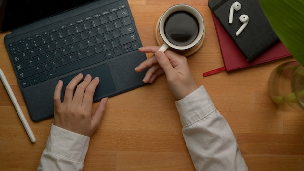Female entrepreneur left hand using digital tablet and right hand holding coffee cup