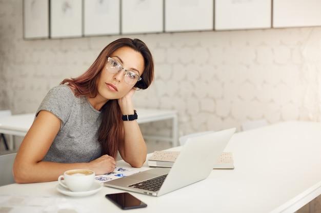 Женщина-предприниматель, управляющая успешным интернет-магазином, использует ноутбук в очках в просторной студии или кафе. концепция фрилансера.